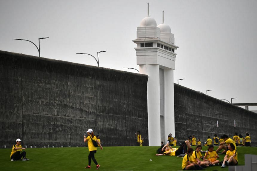 Participants resting and taking photographs outside the old Changi Prison wall at the end of the Yellow Ribbon Prison Run 2019 on Sept 15, 2019.