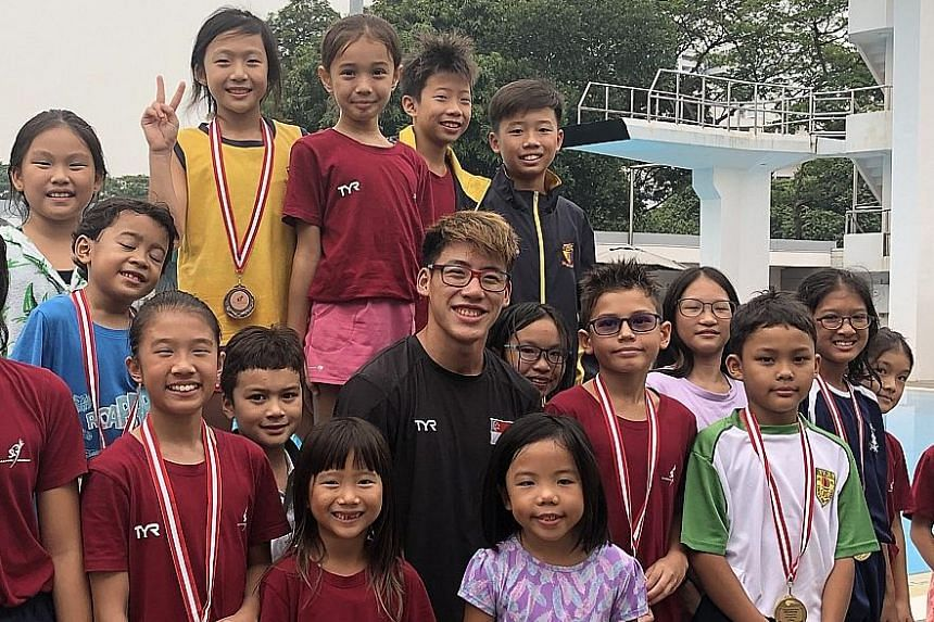 Jonathan Chan, who is the first local diver to qualify for the Olympics, with young competitors at the Singapore Inter-Schools Diving Championships at the Toa Payoh Swimming Complex last Friday.