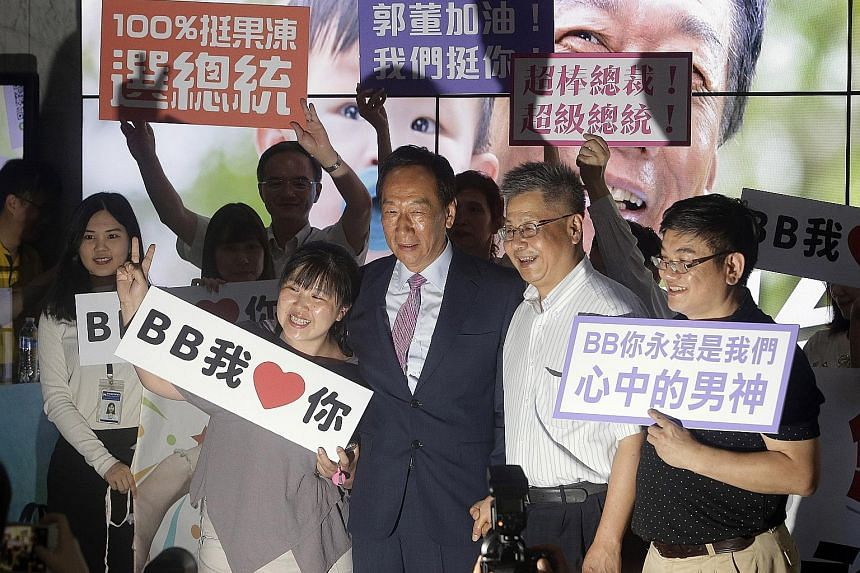 Foxconn founder Terry Gou (in suit) with supporters after the company's annual shareholders meeting in New Taipei City in June. Mr Gou had earlier said that Mazu, goddess of the sea, had told him to run for the presidency.
