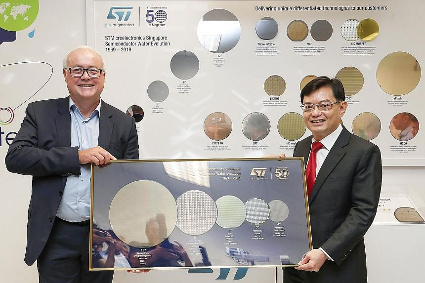 STMicroelectronics chief executive Jean-Marc Chery presenting to Deputy Prime Minister Heng Swee Keat a memento representing the firm's semiconductor wafer evolution over the last 50 years. PHOTO: THE BUSINESS TIMES