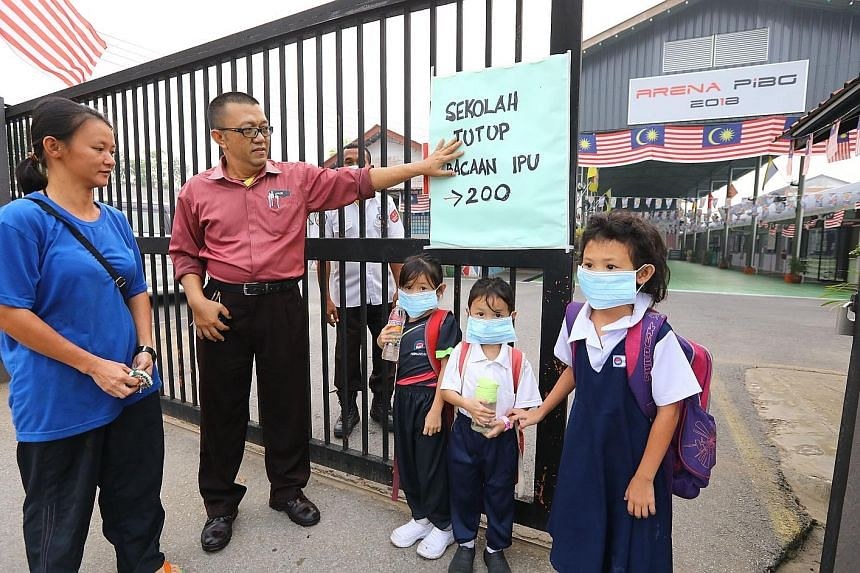 Pupils being told to go home yesterday at a primary school in Kuching, Sarawak, as the Air Pollutant Index (API) crossed the 200 mark. In Sarawak, which is facing the worst of the choking haze over Malaysia, the API reading in the Sri Aman region hit