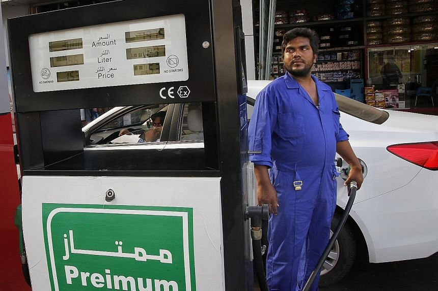 A car being refuelled at a petrol station in the Saudi Arabian port city of Jeddah yesterday. The weekend attacks on oil plants in Saudi Arabia sent crude prices soaring and raised fears of a new Middle East conflict. PHOTO: ASSOCIATED PRESS