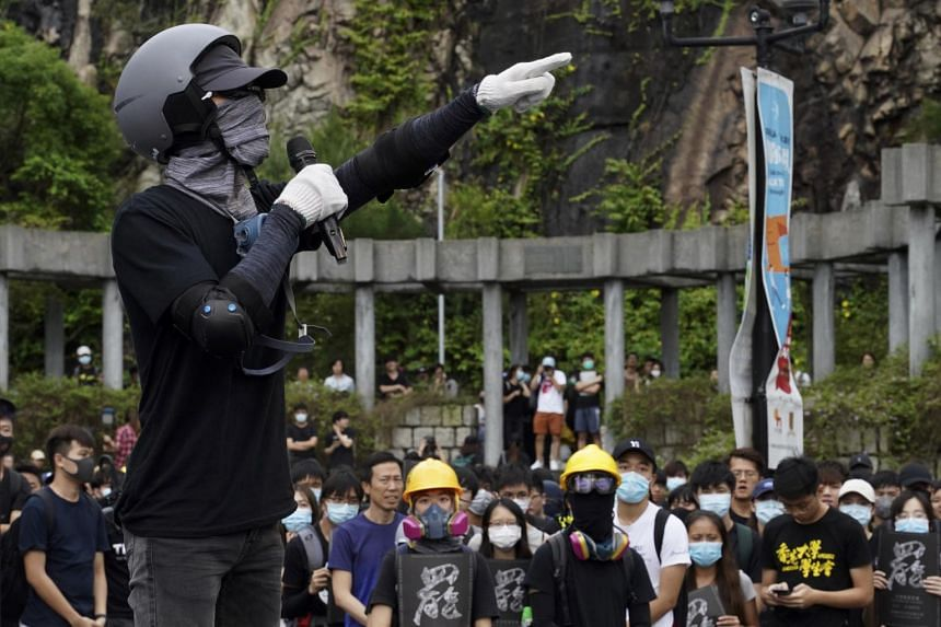 A university student wearing safety gear talks during a strike on the first day of school at the Chinese University in Hong Kong, on Monday, Sept. 2, 2019.