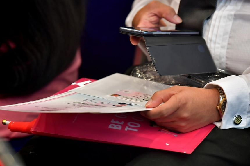 A man taking photos of documents at the National Citizenship Ceremony 2019.