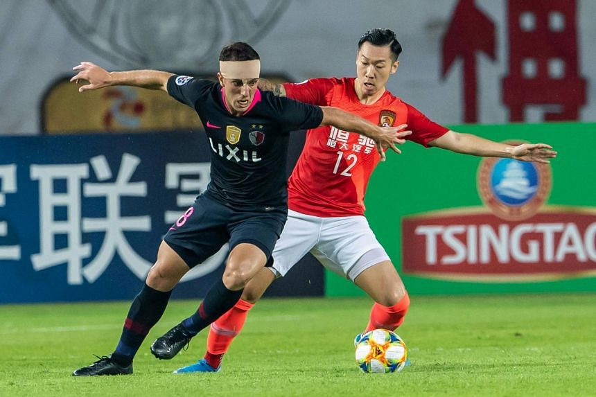 Serginho (left) of Japan's Kashima Antlers fights for the ball with Xu Xin of China's Guangzhou Evergrande during their AFC Champions League quarter-final football match in Guangzhou, on Aug 28, 2019.