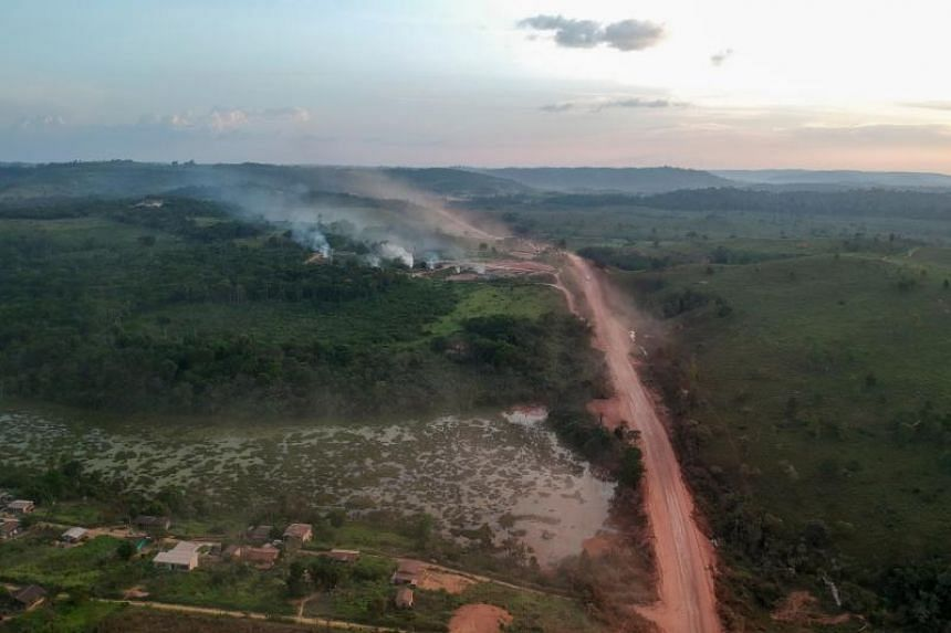 """In this aerial view, red dust of the BR230 highway, known as """"Transamazonica"""", mixes with fires at sunset in the agriculture town of Ruropolis, Para state, northern Brazil, on Sept 6, 2019."""