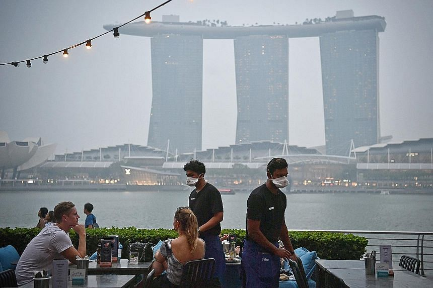 Restaurants with alfresco dining overlooking Marina Bay, such as OverEasy (above) at One Fullerton, say customers have been staying away since last weekend. Staff at OverEasy now wear masks to protect themselves.