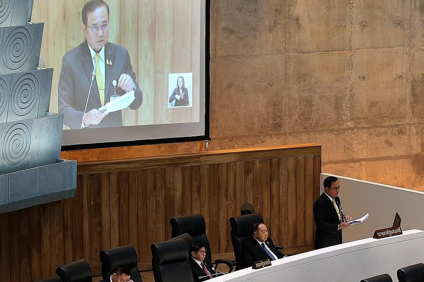 Prime Minister Prayut Chan-o-cha speaking yesterday during the general debate session inside the chambers of the Thai Parliament. He spent 30 minutes defending his economic policies and clarifying the sources of funding for a US$10 billion stimulus p
