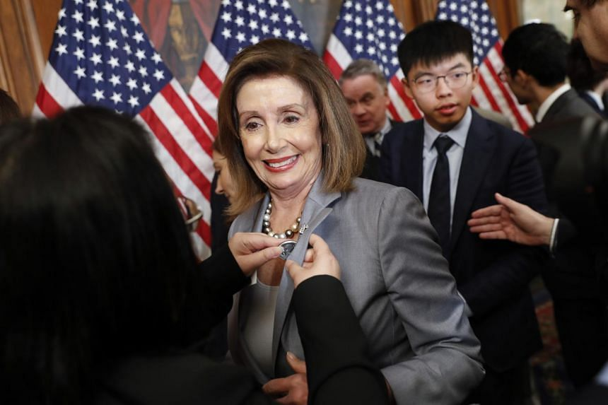 House Speaker Nancy Pelosi is given a lapel pin by a Hong Kong activist following a news conference on human rights in Hong Kong on Capitol Hill in Washington, on Sept 18, 2019.