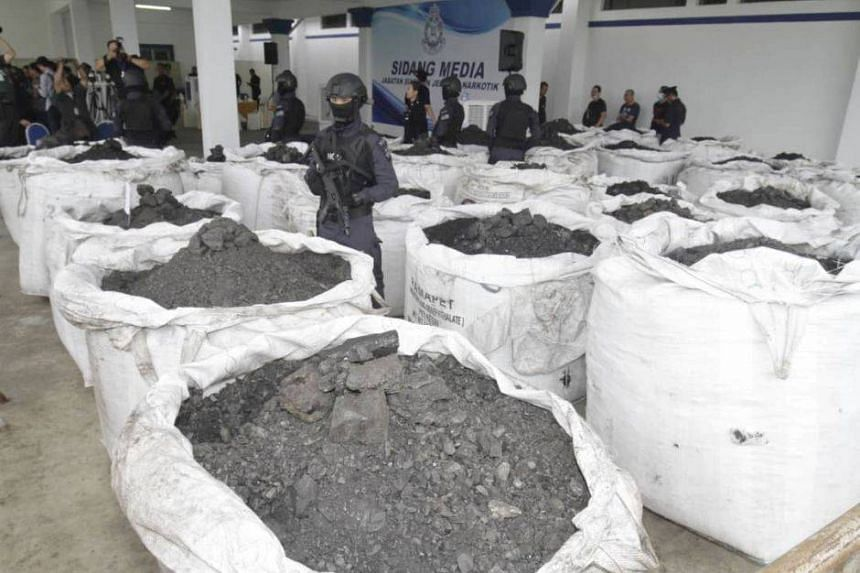 Armed policemen guarding drugs which were mixed within the shipment of coal in Penang on Sept 20, 2019.