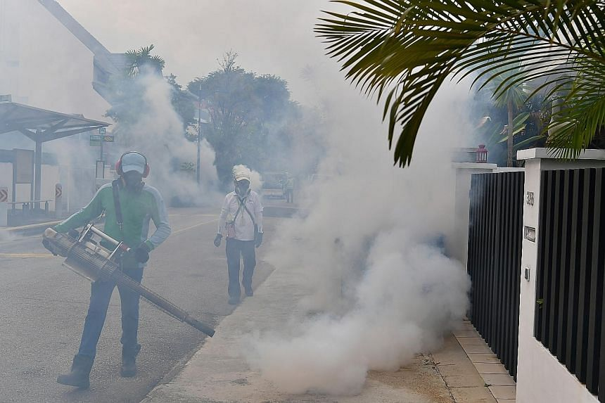 Pest control and National Environment Agency officers carrying out fogging on Sunday in Hemsley Avenue in Serangoon Gardens, where three cases of locally transmitted Zika virus infections were confirmed.