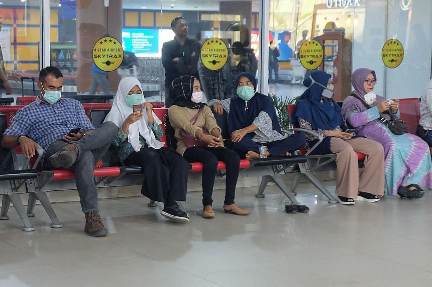 Travellers wearing masks at Pekanbaru's international airport in Riau province yesterday. Two aircraft were yesterday deployed in the city with the discovery of dense clouds that could be seeded to induce rain. ST PHOTO: KHALID BABA