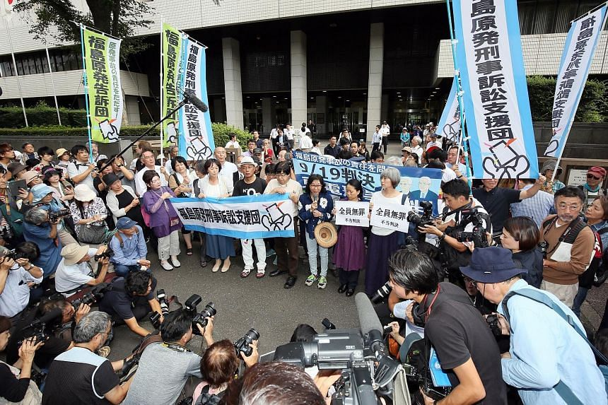 The three former top Tepco executives cleared by the court yesterday are (from left) Sakae Muto, Ichiro Takekuro and Tsunehisa Katsumata. PHOTOS: AGENCE FRANCE-PRESSE Activists rallying outside the Tokyo District Court yesterday as judgment was hande