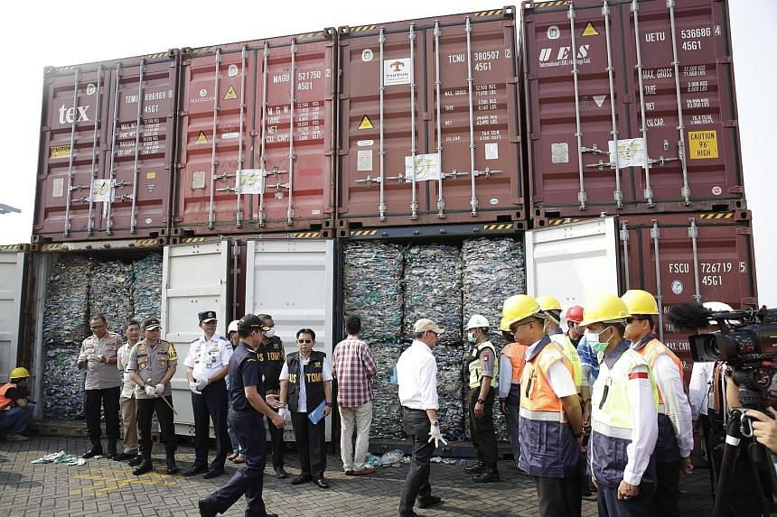 Indonesian officials with the containers of plastic waste meant for recycling, at a press briefing at Jakarta International Container Terminal on Wednesday. Indonesia says the waste was found to contain hazardous substances. PHOTO: EPA-EFE