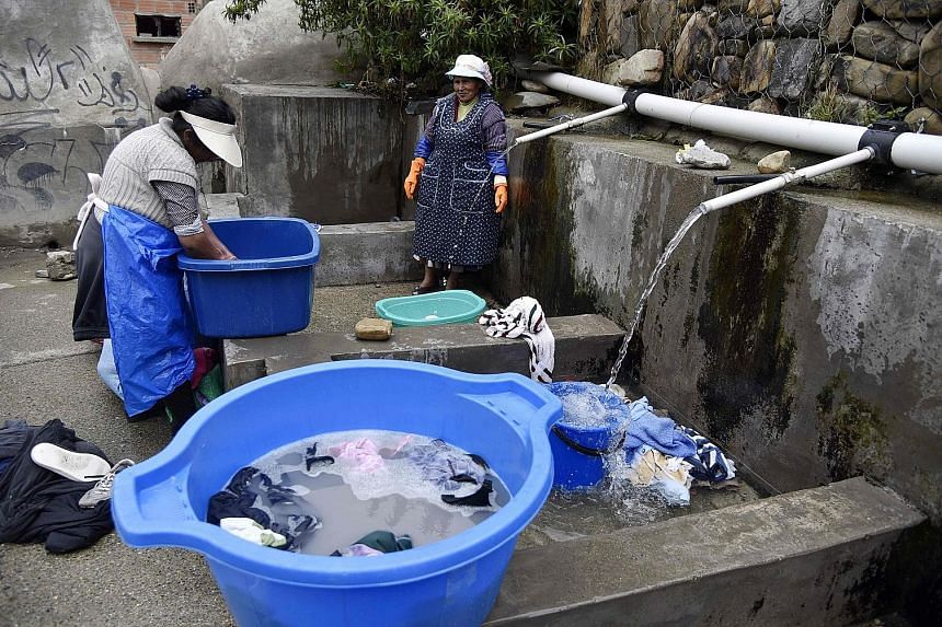 Indigenous women in La Paz washing clothes at a municipal laundry, which uses spring water in order to save supply from the public distribution system. Hit by climate change and a water crisis caused by droughts and bad administration, some communiti
