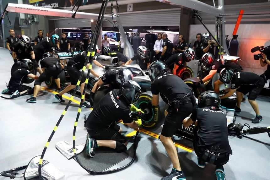 Mercedes engineers attend to a Mercedes car ahead of the Singapore Grand Prix.