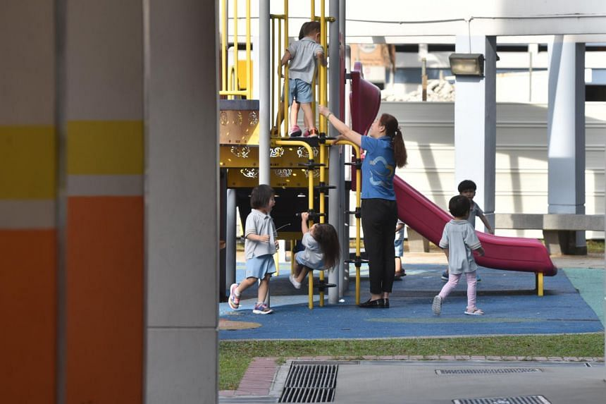 A teacher interacting with preschool children at a playground in Jurong.