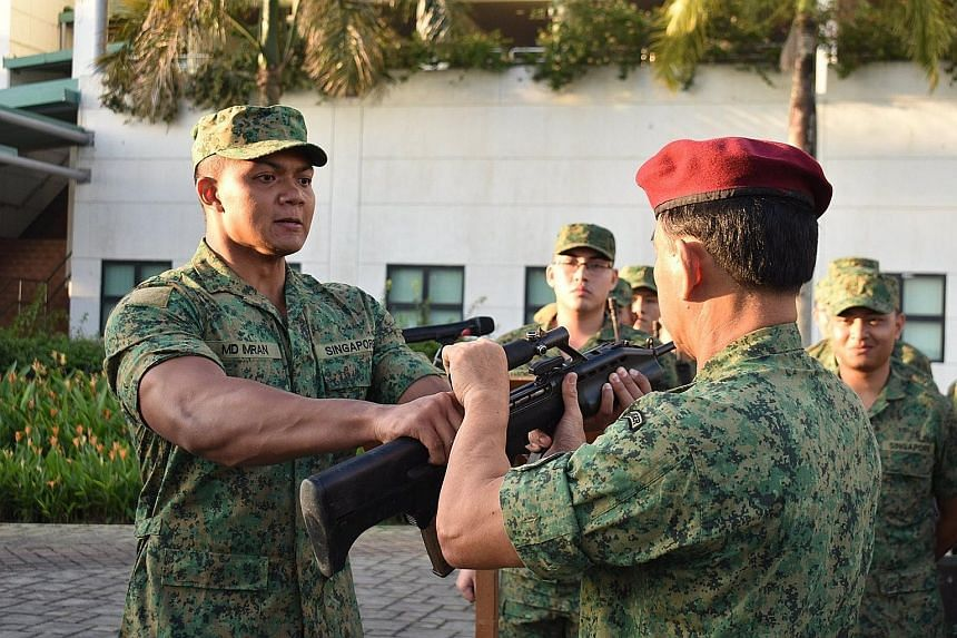 Specialist Cadet Muhammad Imran Azeman with his mother, Madam Rozanah Yassin, and father, Mr Azeman Rahmat, at Pasir Laba Camp yesterday. A photo of him (below) receiving a rifle with his muscular arms from his platoon commander during basic military