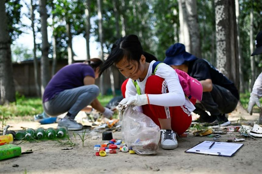 Volunteers collect trash for World Cleanup Day in Beijing on Sept 21, 2019.