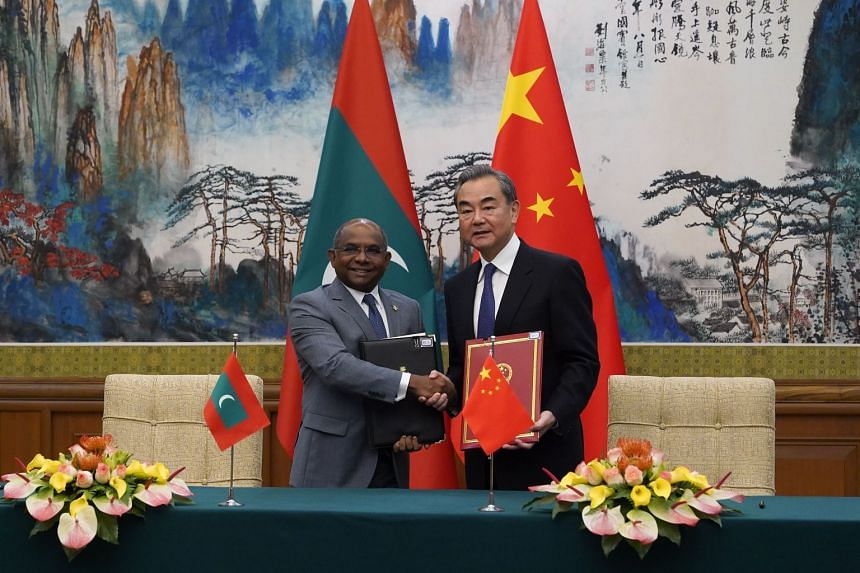 Chinese Foreign Minister Wang Yi and Maldives Foreign Minister Abdulla Shahid hold signed agreements following a signing ceremony at the Diaoyutai State Guesthouse in Beijing on Sept 20, 2019.