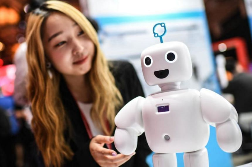 """A woman interacts with """"Pibo"""", a robot at the IFA technology trade fair, the world's largest trade fair for consumer electronics, on Sept 6, 2019."""