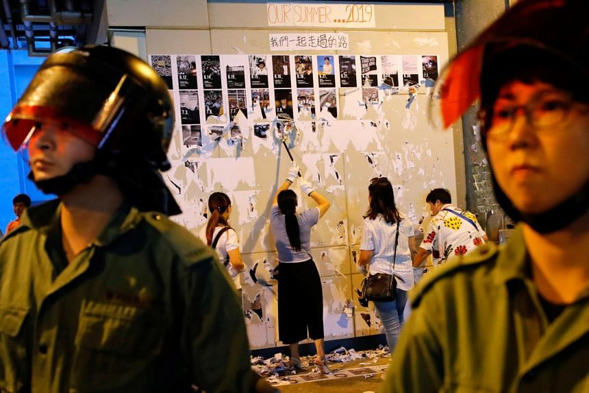"""Riot police are seen in front of China supporters as they pull down """"Lennon Walls"""" of anti-government posters outside Yuen Long MTR station in Hong Kong on Sept 21, 2019."""