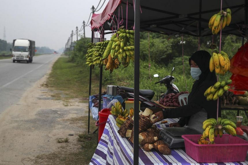 A woman sells fruits at the Johan Setia shrouded by haze in Klang, Selangor, some 40km from Kuala Lumpur, Malaysia, on Sept 18, 2019.