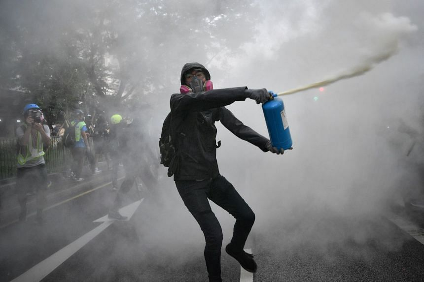 A protester uses a fire extinguisher to slow down the police advancement during a rally in Hong Kong's Tuen Mun district on Sept 21, 2019.