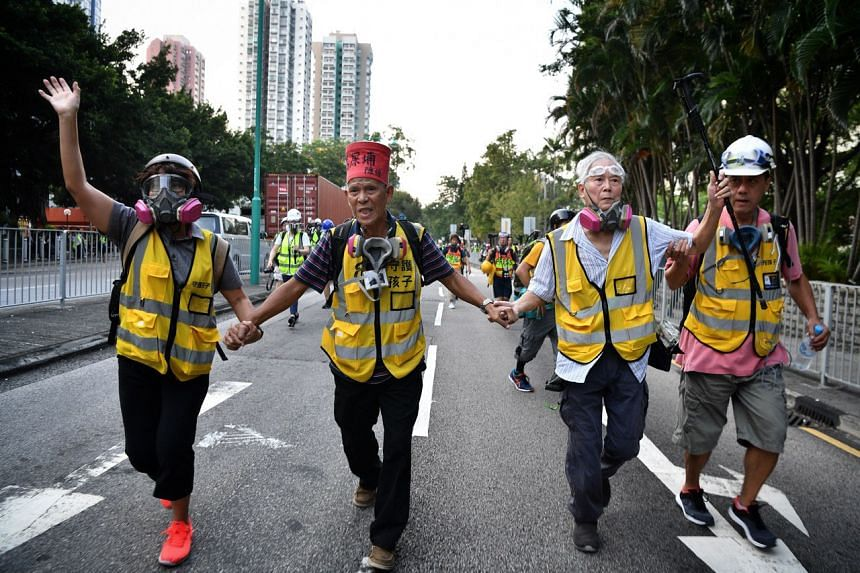 Volunteers form a barrier to slow down police officers and buy time for other protesters to leave during a rally in Hong Kong's Tuen Mun district on Sept 21, 2019.