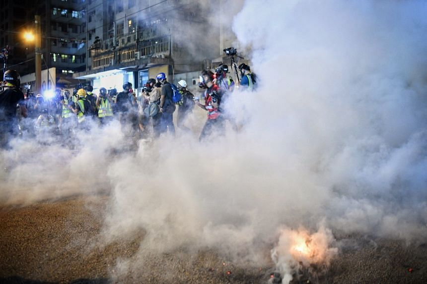 The press photographers scrambled as a tear gas canister exploded near them in castle peak road Yuen Long.