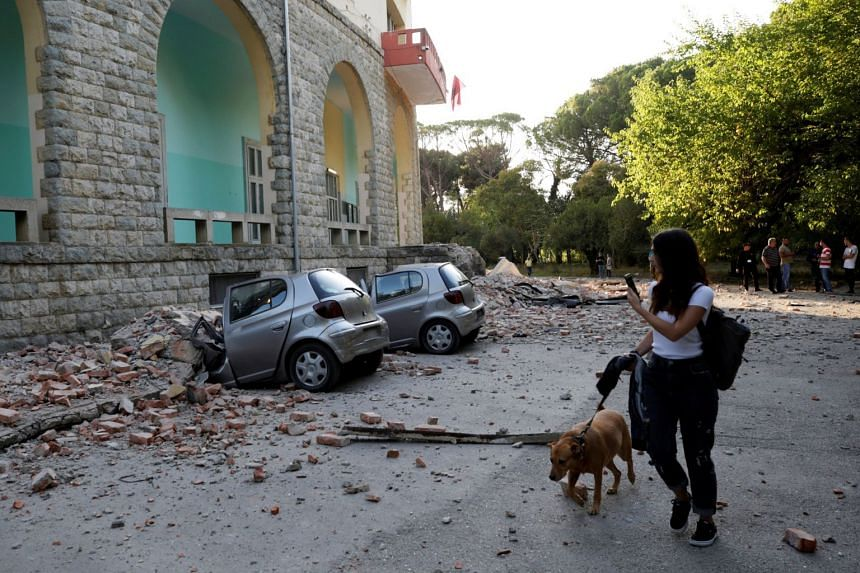 A woman with a dog walks past destroyed cars and a damaged building after an earthquake in Tirana.