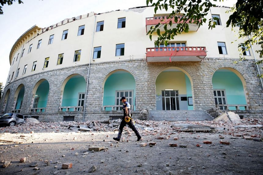 A police officer walks past a damaged building after an earthquake in Tirana.