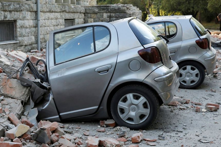 Destroyed cars stand next to a damaged building after an earthquake in Tirana.