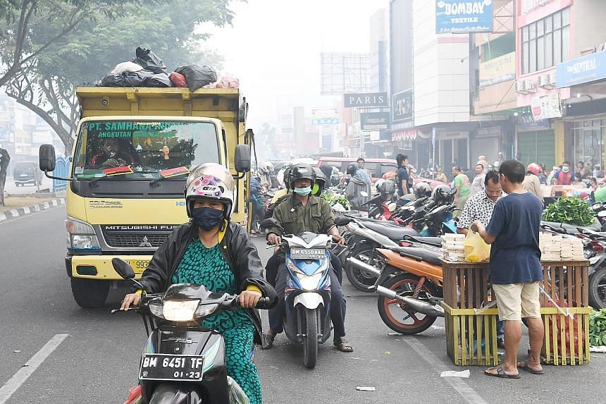 Masked motorcyclists near Agus Salim market in Pekanbaru at around 7.30am yesterday. Far left: Mr Bakri Hamid (far left) and his neighbour, Mr Jimi Azmi, 25, by the Siak river in Pekanbaru. Mr Bakri says when he wakes up, he feels like he has just sw