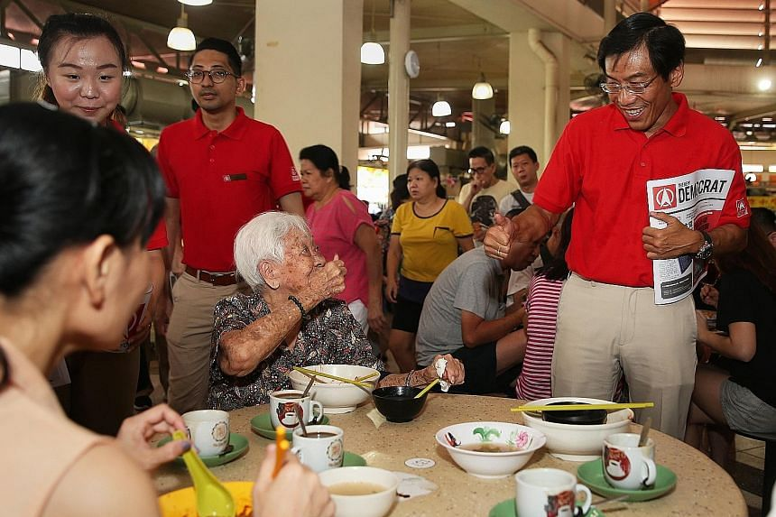 Singapore Democratic Party's Dr Chee Soon Juan and an elderly resident giving each other the thumbs up during his walkabout in Yuhua with party members on Aug 4. SDP plans to launch its manifesto soon and hold a pre-election rally next month.