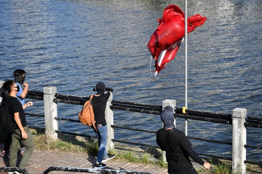 Protesters tossing a defaced mainland Chinese flag into Shing Mun River near New Town Plaza in Sha Tin in Hong Kong on Sept 22, 2019.