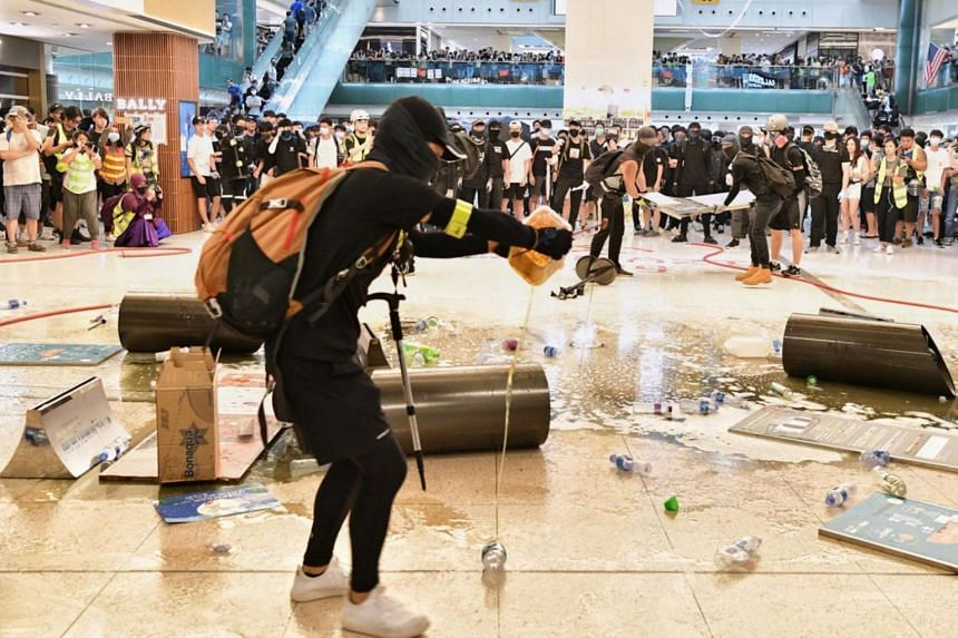 Protester pouring oil onto the floor to make it slippery in an effort to slow police advancement in New Town Plaza, Sha Tin in Hong Kong on Sept 22, 2019.