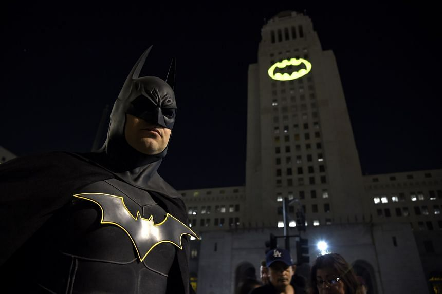 A 2017 photo shows a man dressed as the DC Comics character Batman in front of a projected bat signal.