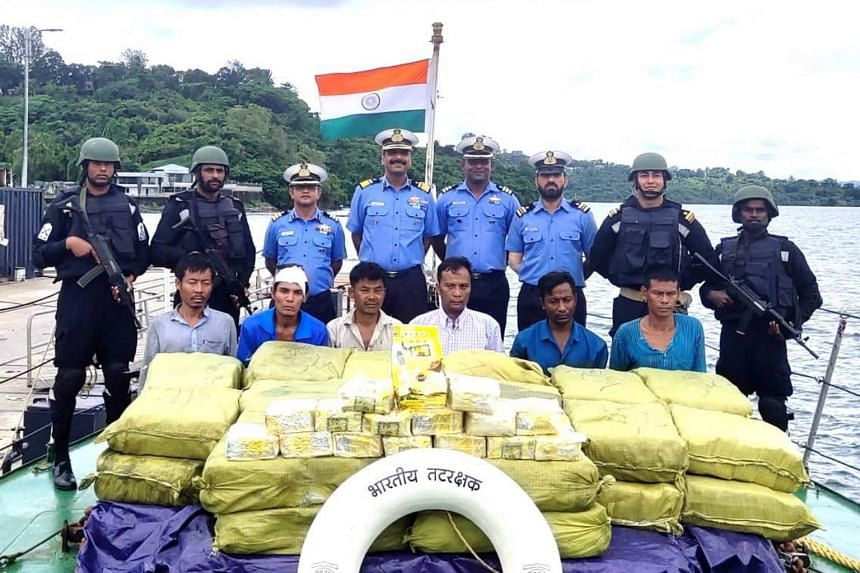 Indian Coast Guards (back row) pose with the arrested boat's crew and the seized drugs, near Nicobar Islands, India, on Sept 19, 2019.