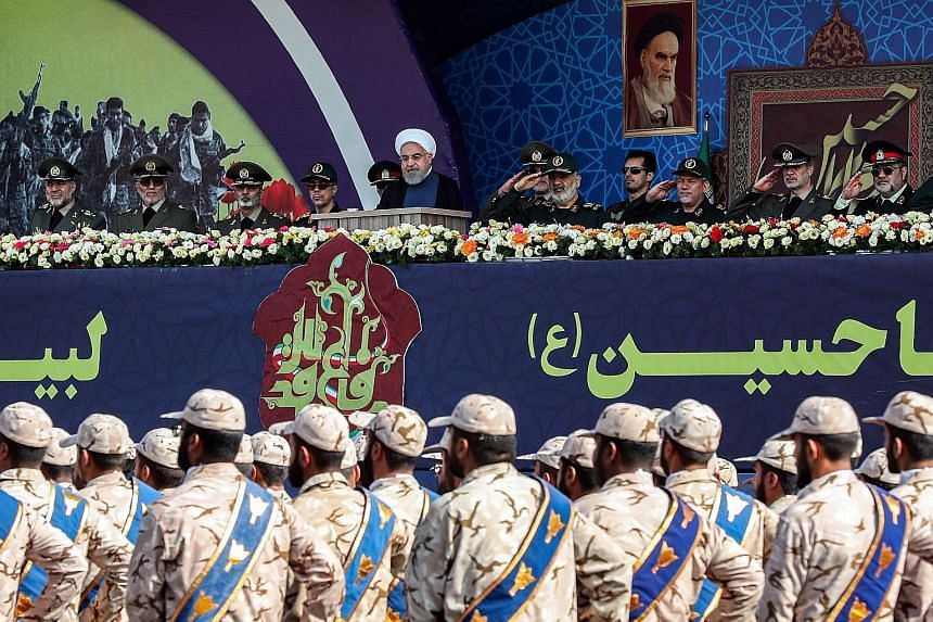 Above: A cameraman on a trip organised by Saudi Arabia last Friday filming Aramco's oil processing facility in Abqaiq which had been hit by a Sept 14 attack. Left: Iran's President Hassan Rouhani (centre) and other military commanders watching a marc