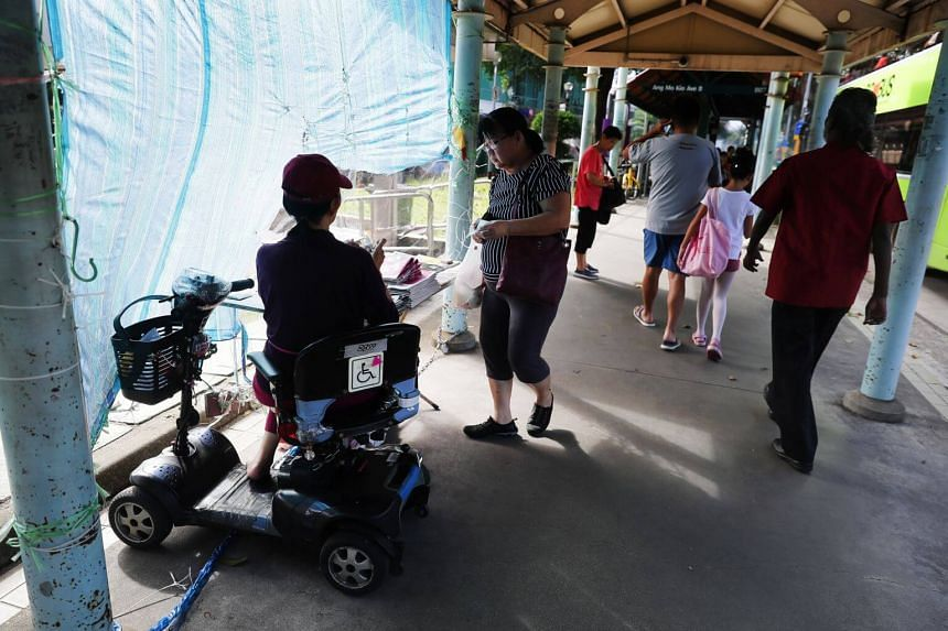 A newspaper seller on a personal mobility aid near Ang Mo Kio MRT, on Aug 25, 2018.