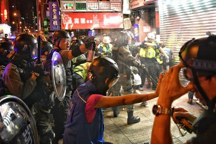 A police officer uses pepper spray on members of the media along Nathan Road in Hong Kong on Sept 22, 2019.