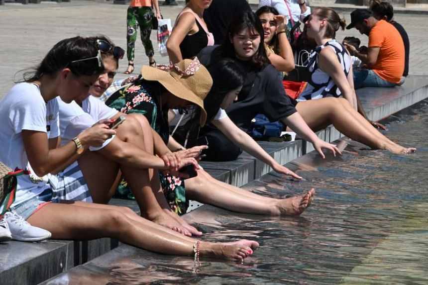 In a photo taken on June 26, 2019, tourists refresh themselves in a pond near the Louvre in Paris.