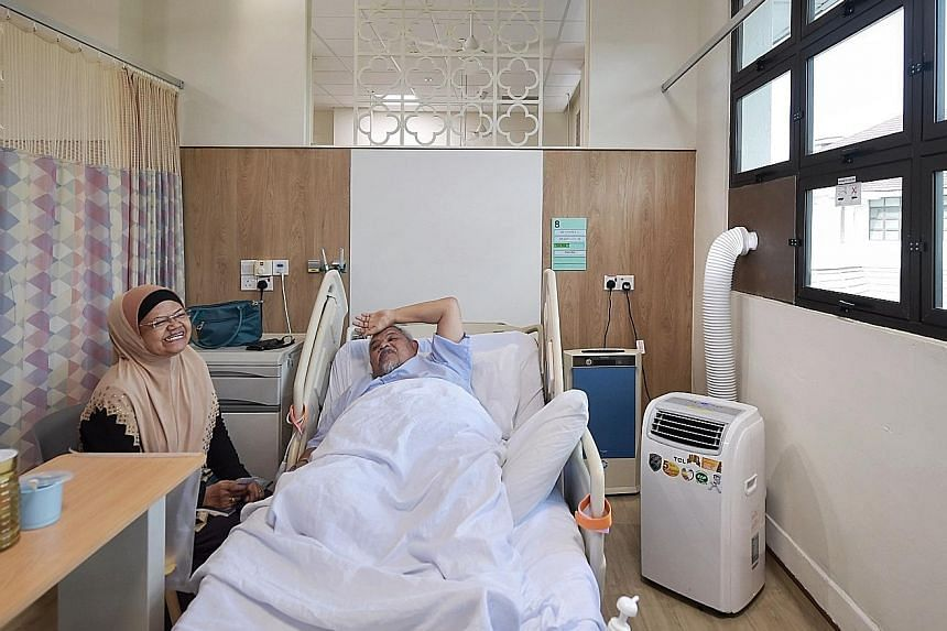 Senior security officer Haron Jasmin is safe at Alexandra Hospital with a portable air-conditioning unit and an air purifier (blue) providing ventilation. Beside him is his wife Rabiah Tik, 65, who was visiting yesterday. ST PHOTO: KUA CHEE SIONG Peo