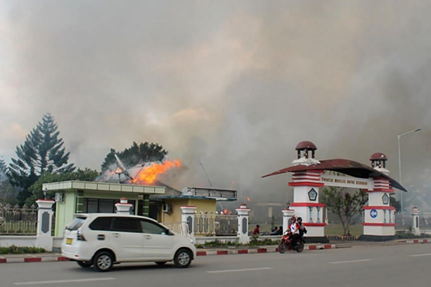 A car passes governor office building of Jayawijaya burned during a protest in Wamena, Papua, Indonesia, on Sept 23, 2019.