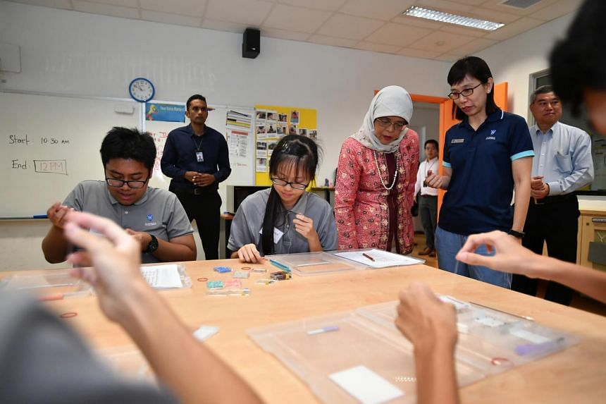 St Andrew's Autism School teacher Karen Seow (right) explaining to President Halimah Yacob how beading keeps students like Zhafran Murat and Sharlyne Lee meaningfully engaged and prepares them for work and independence after school.