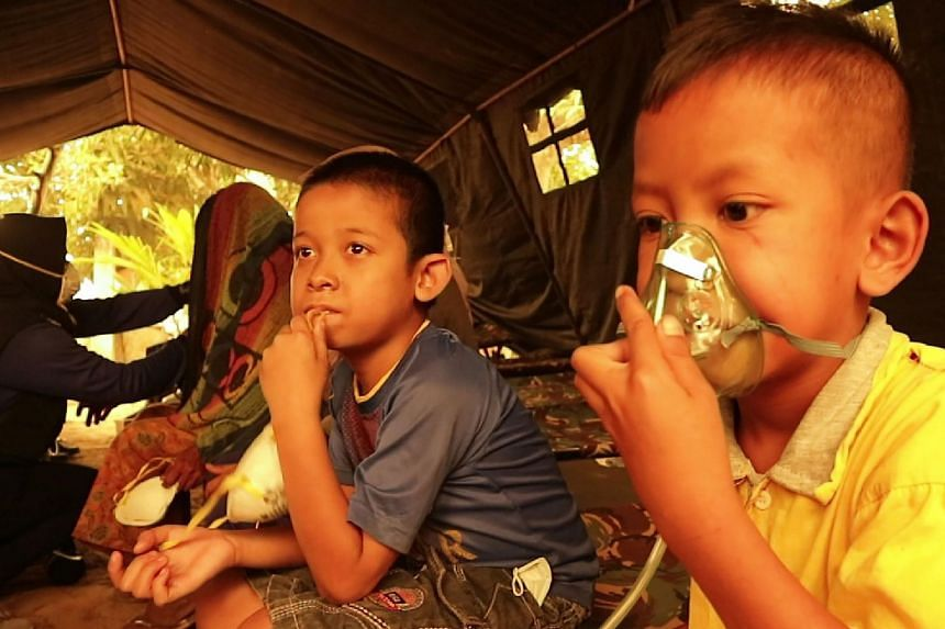 Children get a dose of oxygen from a Red Cross volunteer at a village in Jambi on Sept 24, 2019.