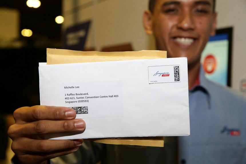 A postman holds a letter with a smart stamp attached at Suntec Convention Centre, on Sept 24, 2019.