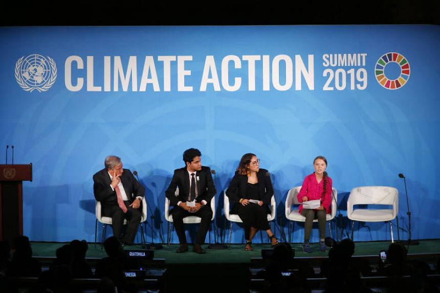 United Nations Secretary-General Antonio Guterres (left) and young environmental activists look on as Greta Thunberg addresses the UN Climate Action Summit in New York on Sept 23, 2019.