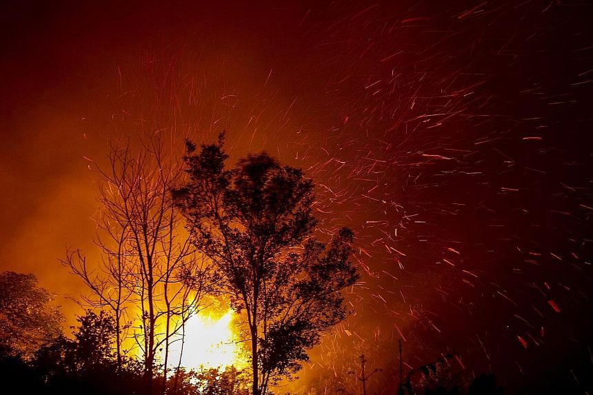 Left: A fire burning in Palangkaraya, in Central Kalimantan, on Monday. An online report at the weekend said fires had been detected in concessions belonging to pulp giants Asia Pacific Resources International Holdings and Asia Pulp and Paper. The th